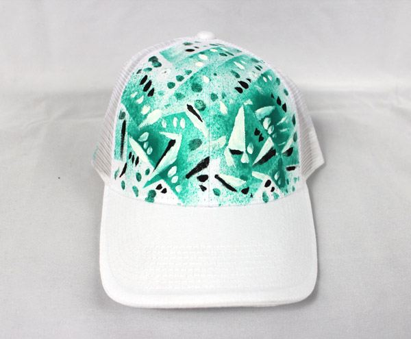 12829434cd4 Make sure to tape up the hat and spray in a controlled area to avoid  unwanted overspray. After the back ground paint was dry we embellished it  by hand ...